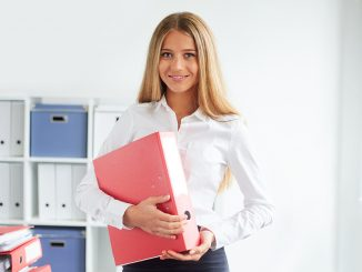 Young Business Woman Standing In Office With Folders